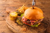 BURGER ANGUS BEEF - juicy veal, cheddar cheese, bacon, iceberg, pickled cucumber, Mexican hot peppers, fried onion, tomato, burger sauce. Served with fried potatoes and rosted corn