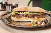 КАРНИТАС ----- бавно сготвена свинска плешка в сок от портокал и подправки, мачкан боб, гуакамоле, майонеза, червен лук, халапеньо, пико де гайо, панини хляб