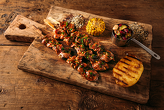 LIMB NECK SKEWERS - glazed with smoked sauce, served with colored bean with pickled cucumbers, roasted corn, baked potatoes with herbs butter and BBQ sauce